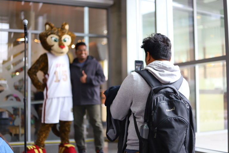 A student taking a picture of another student standing with IUPUI's mascot, Jazzy.